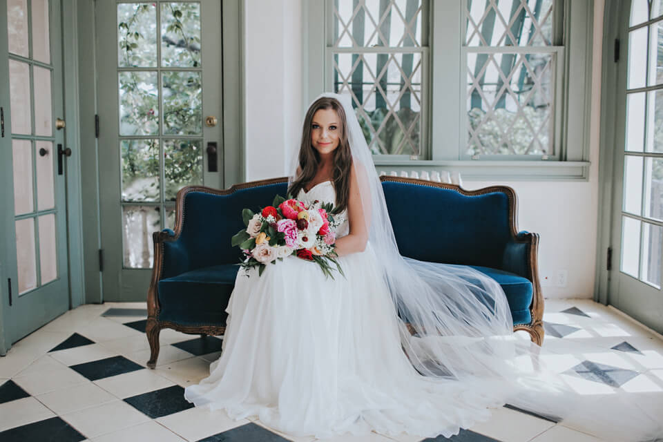 bride holding floral bouquet on blue velvet couch