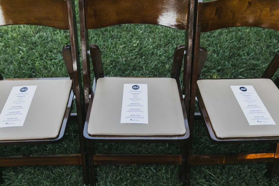 modern wedding program in dark wooden chair