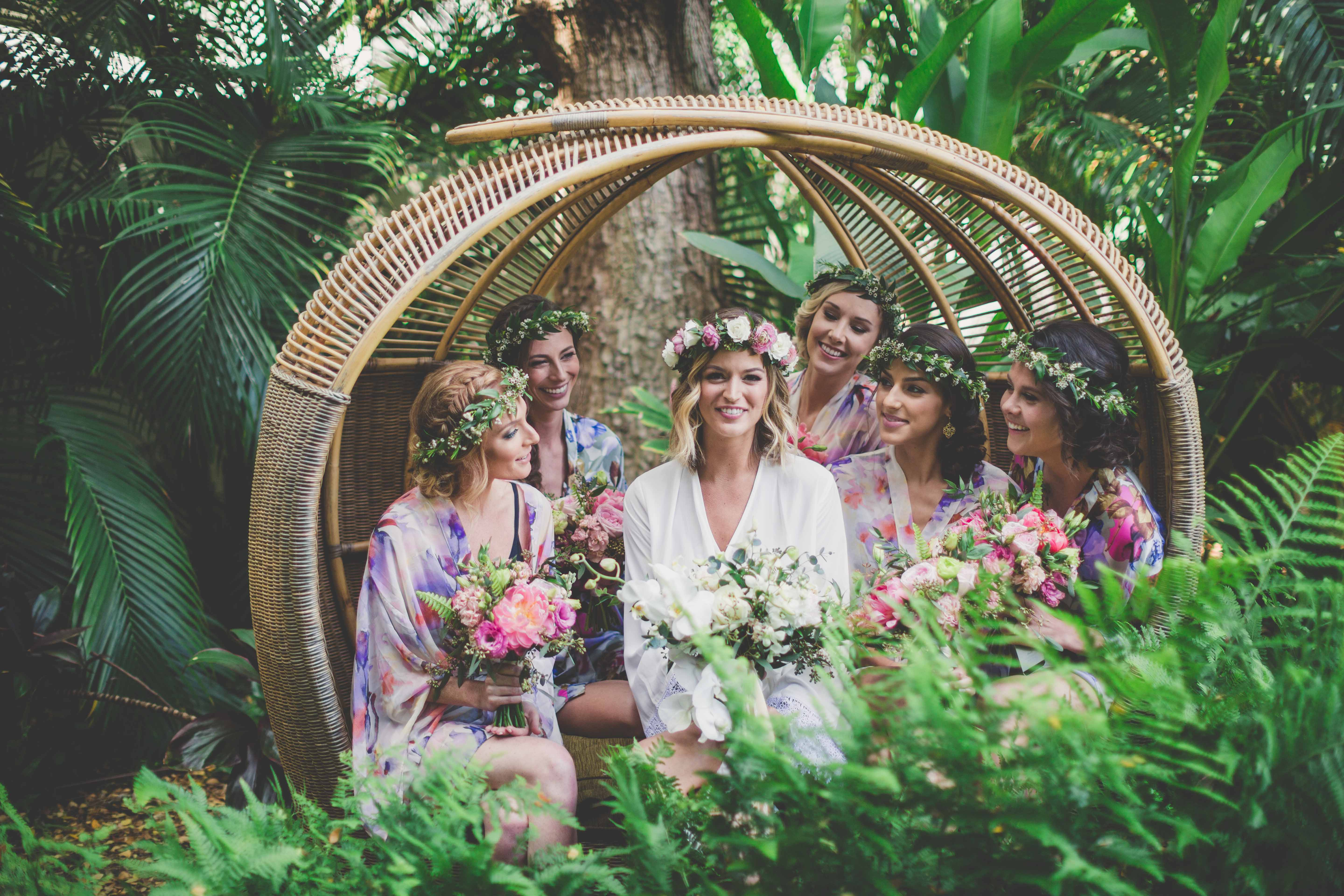 bride with bridesmaids in flower crowns in rattan circle chair