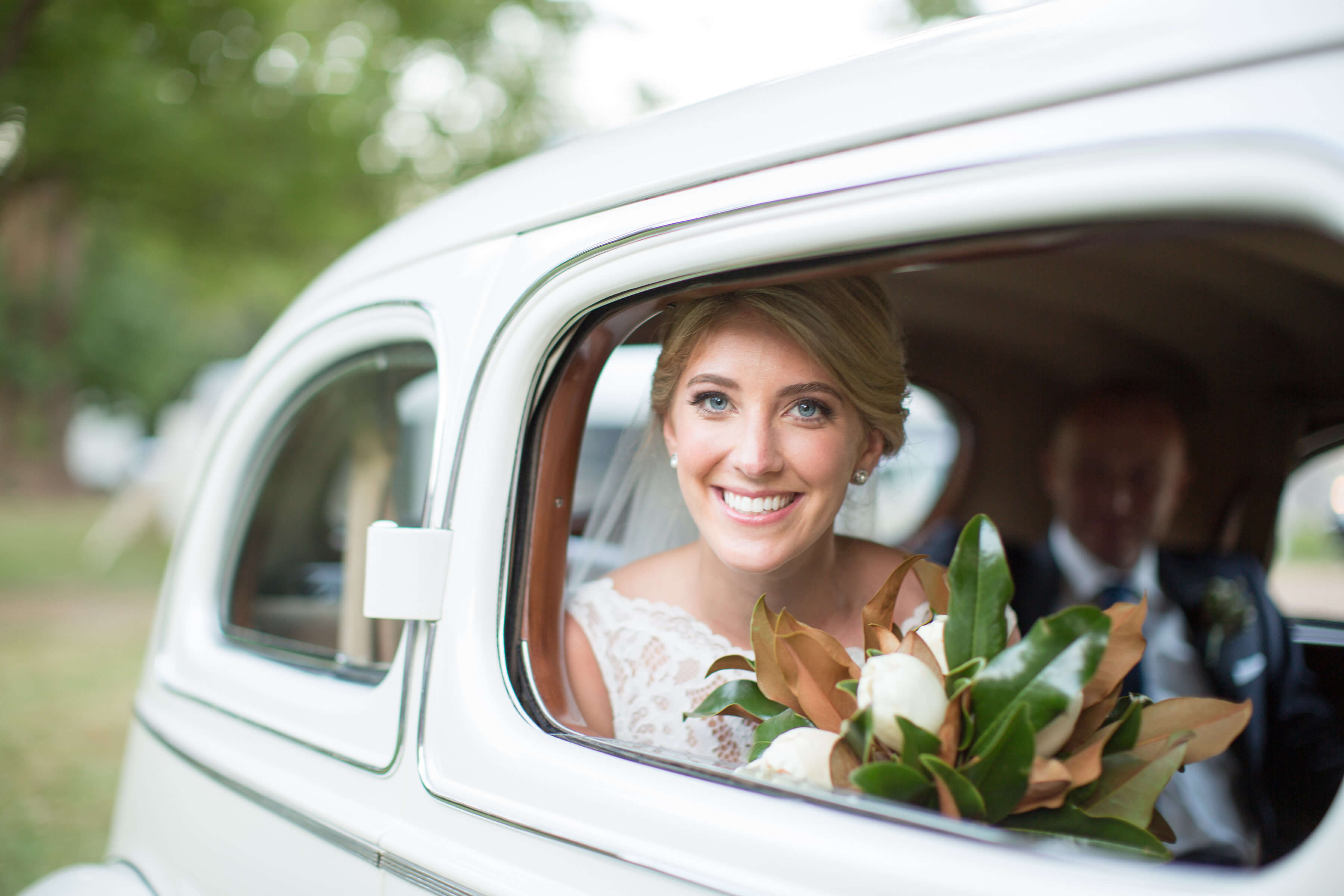 bride and groom in old white car