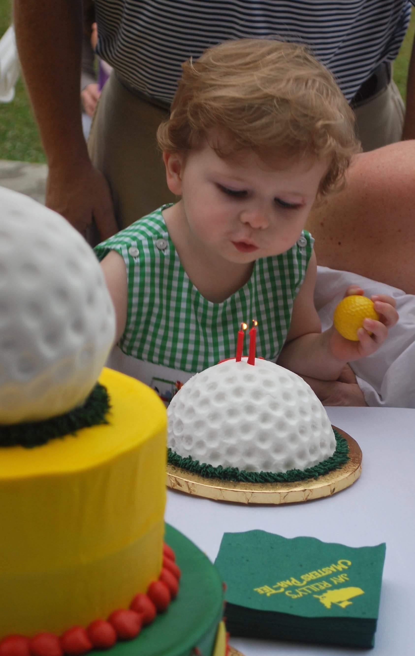 Blowing out candles on golf birthday cake