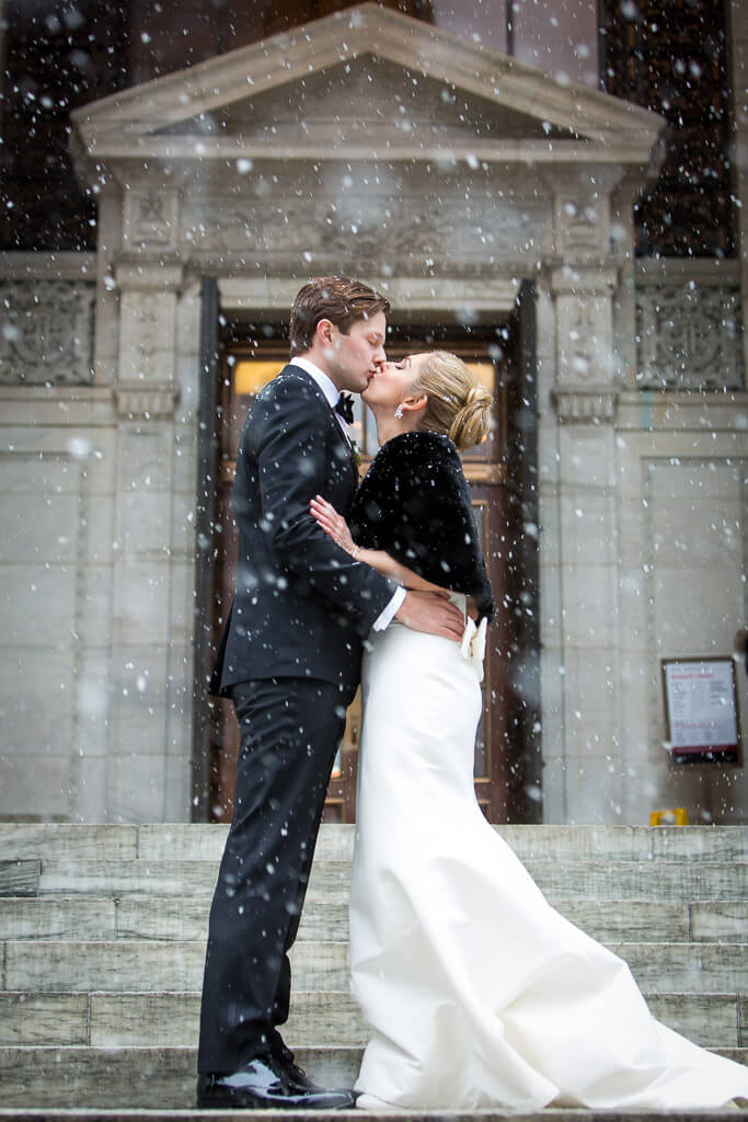 bride in fur capelet kissing groom in tuxedo with snow falling