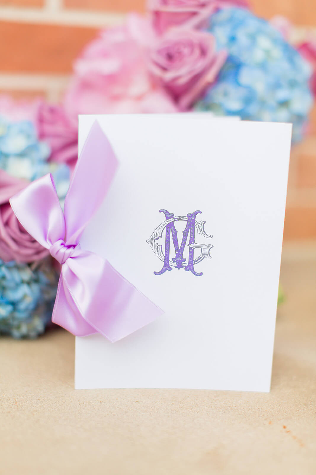 Monogrammed wedding ceremony program with bow