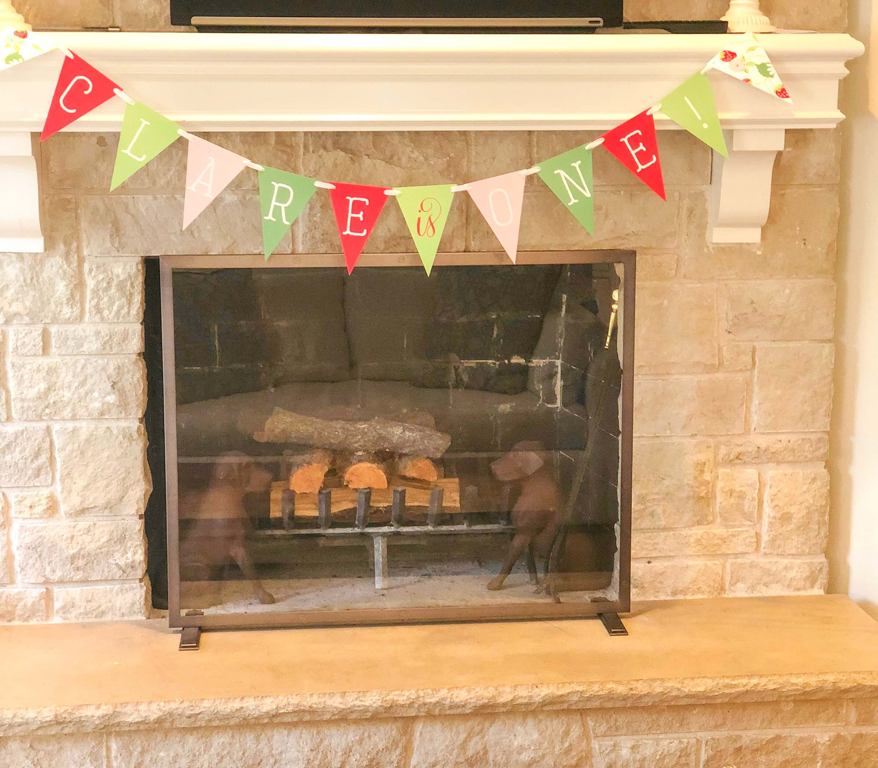 strawberry birthday banner hanging on mantle